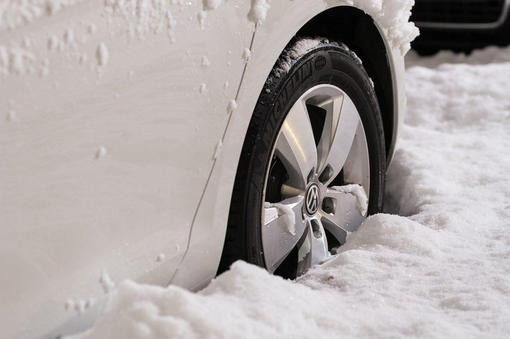 Jak przygotować samochód do zimy? Zadbać o opony! Opona zimowa w śniegu. Samochód zaparkowany w głębokim śniegu.